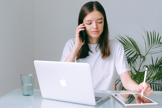 A caucasian woman in a white crew neck shirt is sitting in front of a silver macboo while talking on the phone and taking notes on a tablet.