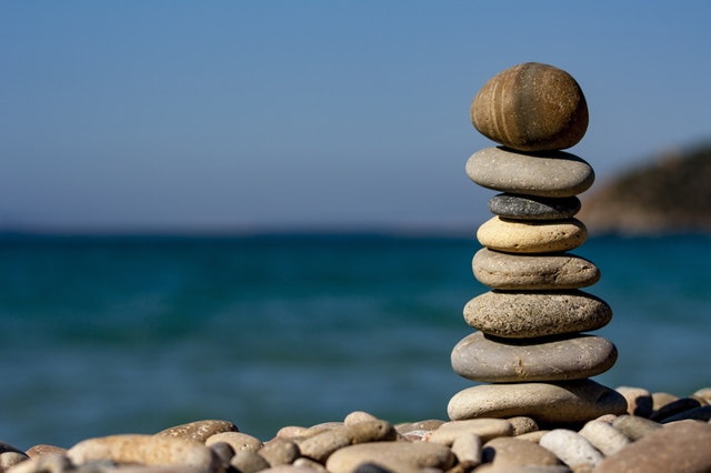 Eight smooth stones balanced on top of each other against a blurred background featuring the sky and a body of water.
