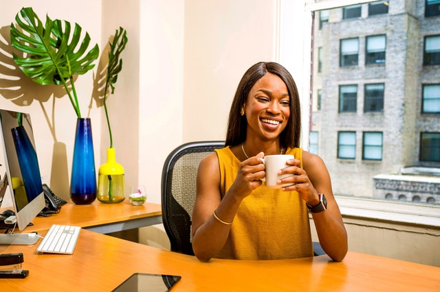 A black woman wearing a mustard color blouse sitting at an office computer desk. She is smiling towards the camera and holding a coffee mug with both hands.