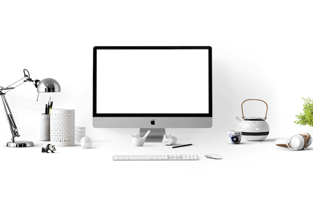 A photo of a white desk against a white wall with a silver lamp, pencil cups, an iMac computer and keyboard, a tea kettle, and a teacup.