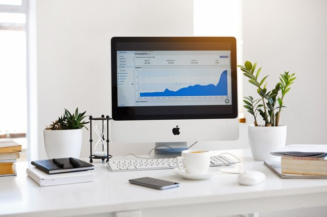 An iMac desktop computer with an analytics dashboard on the screen, sitting on top of a computer desk with plants, coffee, books, and other objects on the desk.