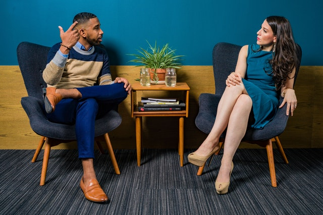 A male in a sweater, jeans, and loafers is sitting in a blue chair across from and talking to a woman in a blue dress and tan heels.
